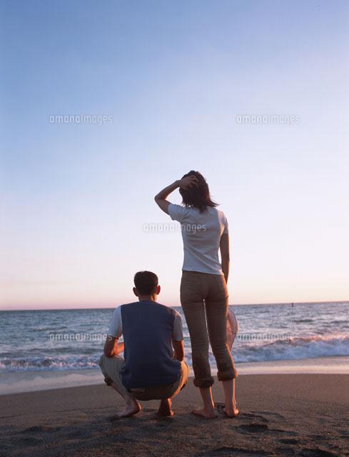 海を眺めるカップルの後ろ姿 の写真素材 イラスト素材 アマナイメージズ