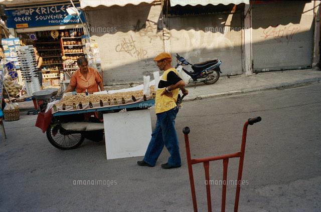 路上で物を売る女性と通行人02265034020の写真素材イラスト素材