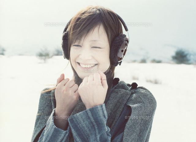 耳覆いをして笑う日本人女性[022...