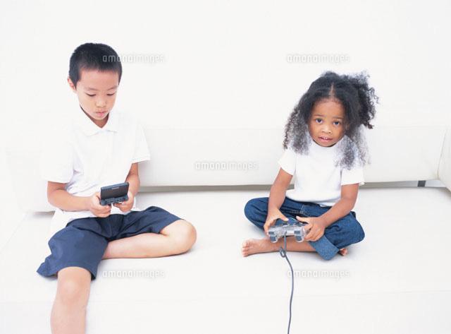 ゲームをする日本人の男の子と外国人の女の子02299001683の写真素材