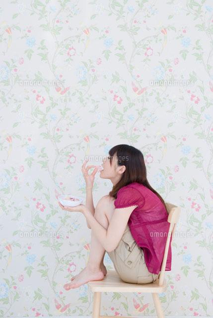 椅子に座ってお菓子を食べる女の子02299006651の写真素材イラスト