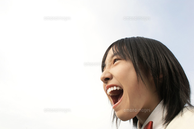 大きく口を開けて叫ぶ女子学生07045000182の写真素材