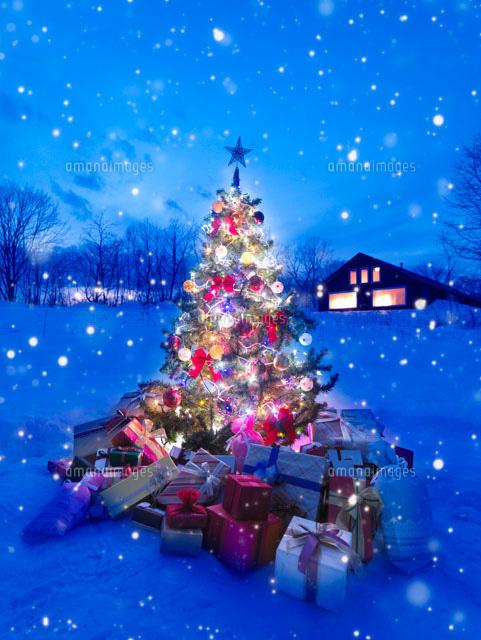 雪の中の光り輝くクリスマスツリーとたくさんのプレゼント20027006757