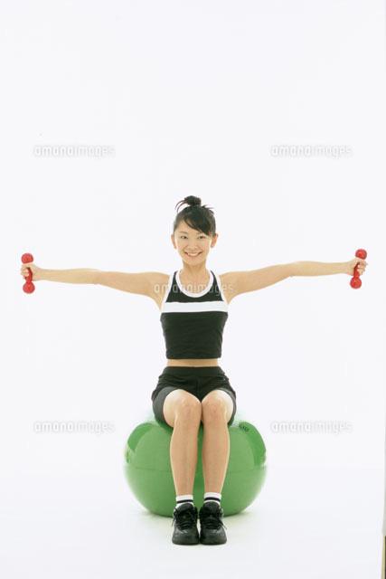 バランスボールに座るダンベルを持つ女性20035000110の写真素材