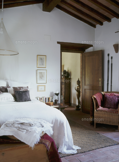 Bed With White Bedspread And Wicker Chair In Simple Bedroom (c)Heinze,  Winfried