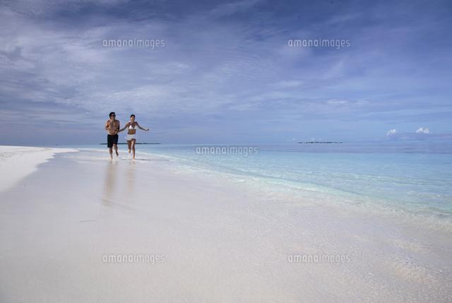 couple at a beach at coco palm dhuni kolhu resort in maldives