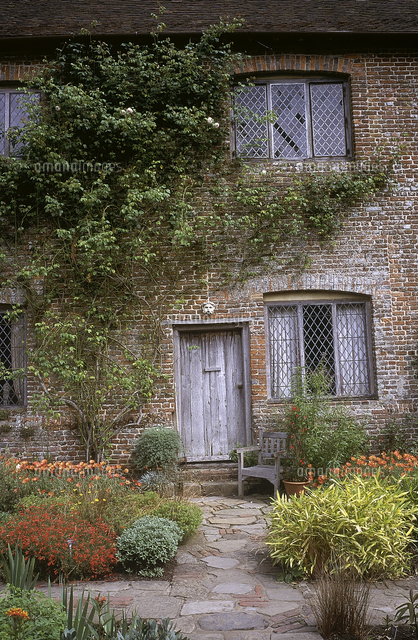 entrance of country house with red flowers in front great dixter