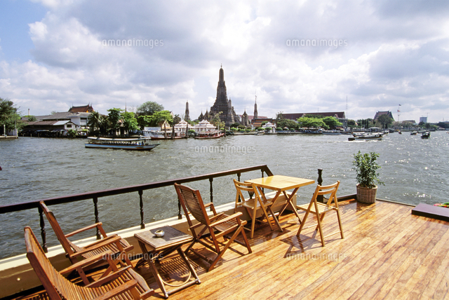 view of river boats buildings and temples from deck of boat in