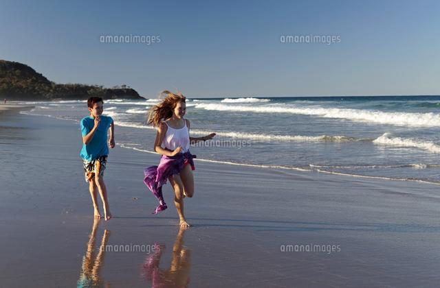 teenage boy and girl run along sunshine beach noosa queensland