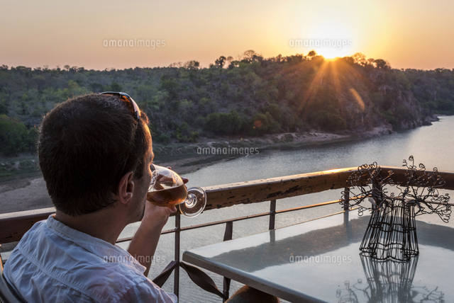 Africa, Zimbabwe, Gonarezhou National Park. Tourist enjoying a beer at sunset looking out over the S