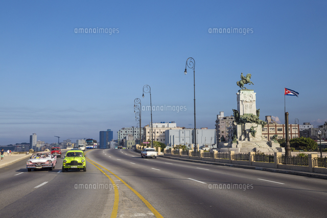 Cuba, Havana, Malecon, Classic American cars passing by Monument to Lieutenant-General Antonio Maceo