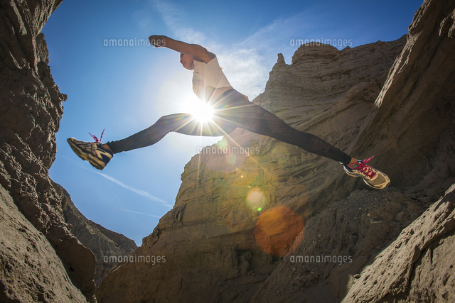 Young woman jumping in canyon