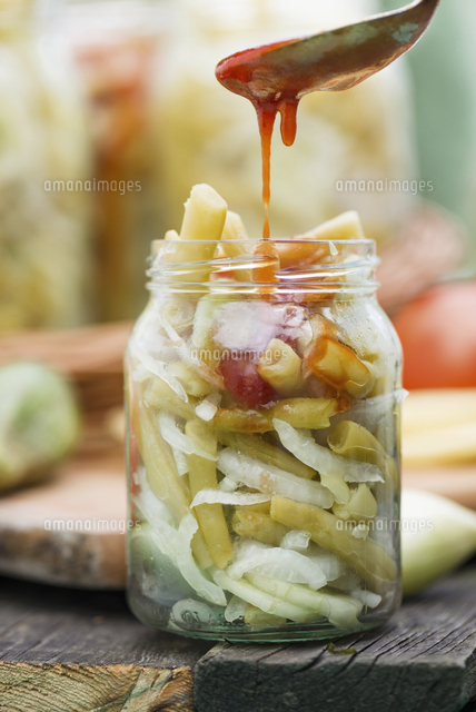 bean and cucumber salad with onions and tomato sauce in a jar