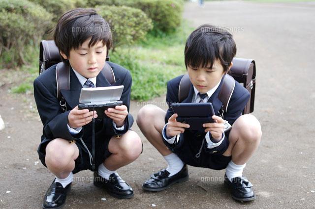 ゲーム機で遊んでいる小学生の男...