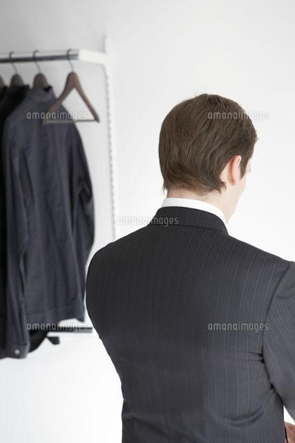 室内でスーツに着替えた男性の後姿24014000109の写真素材イラスト