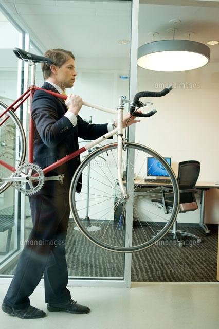 オフィスに自転車を運び入れるビ...