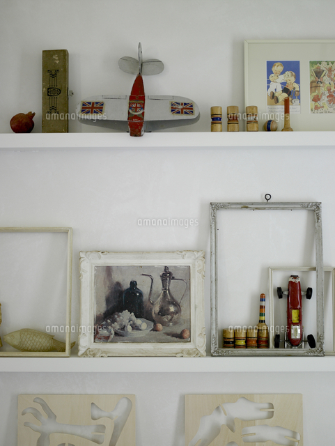 white shelves with picture frames and old toys in residential house
