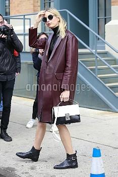Karolina Kurkova wears a mahogany knee length leather coat at the Carolina Herrera New York Fashion