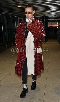 Bella Hadid arrives at Heathrow Airport weaing a polka dot print vinyl trench coat from the Prada SS