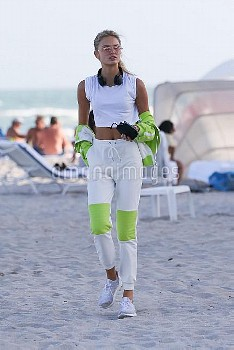 Victoria's Secret model Romee Strijd wears a neon-accented sporty outfit as she leaves the beach in