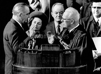 President Lyndon Johnson takes the oath of office at his 1964 Inauguration. L-R: President and Lady