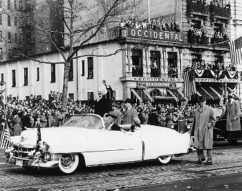 Newly inaugurated President Dwight Eisenhower waves to crowds from an open car. First Lady Mamie Eis