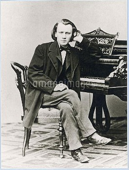 Johannes Brahms, German composer and musician, seen here as a young man, sitting at a grand piano.