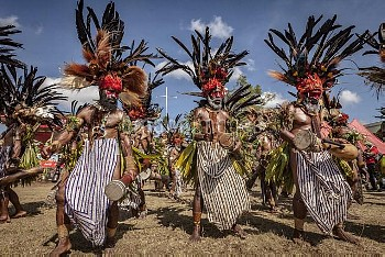 Men in ritual make-up and traditional clothing dancing during a sing-sing, Goroka Show, Goroka, East