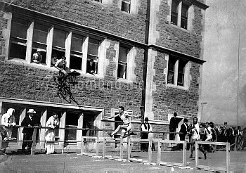 USA's Harry Hillman (l) races to victory, watched by inhabitants of St Louis from their windows
