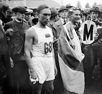 Hannes Kolehmainen of Finland draped in the Finnish flag and crowned with a wreath of laurels after
