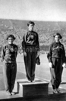 (L-R) The medallists stand on the podium for the playing of the winner's national anthem: silver med