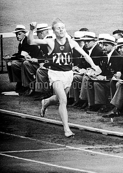 USSR's Vladimir Kuts celebrates as he crosses the line to win gold