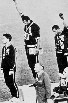 USA's gold and bronze medallists, Tommie Smith (c) and John Carlos (r), bow their heads and raise bl