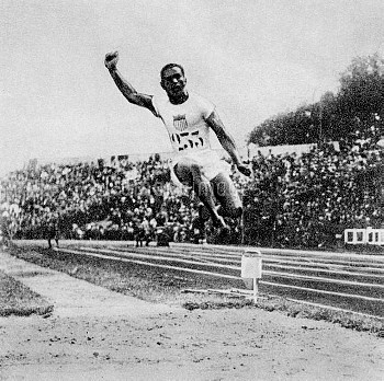 USA's William DeHart Hubbard leaps to a gold medal with a jump of 7.45m