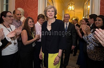 Staff clap as new Prime Minister Theresa May, followed by her husband Philip John, arrives at 10 Dow