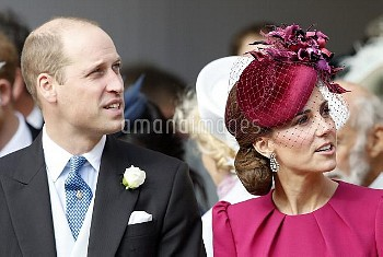 The Duke and Duchess of Cambridge, look up at the Royal Standard flying from the round tower followi