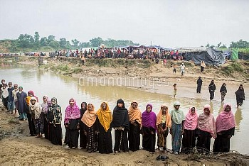 Rohingya Muslims who have escaped violence in western Myanmar stand near a stone that marks no man's