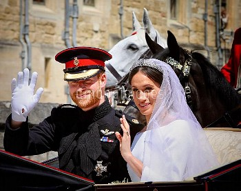 WINDSOR, ENGLAND - MAY 19: Prince Harry and Meghan Markle travel through the streets of Windsor in a