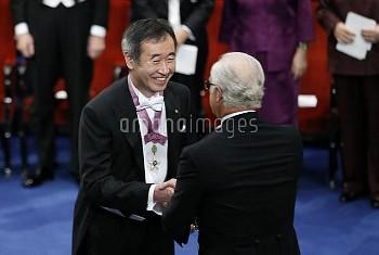 STOCKHOLM, Dec. 10, 2015 (Xinhua) -- 2015's Nobel laureate in Physics Takaaki Kajita (L) receives hi