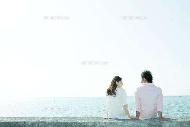 海沿いに座るカップルの後姿 a の写真素材 イラスト素材 アマナイメージズ