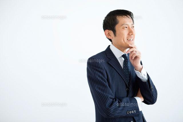 顎に手をあてるビジネスマン07800016132の写真素材イラスト素材