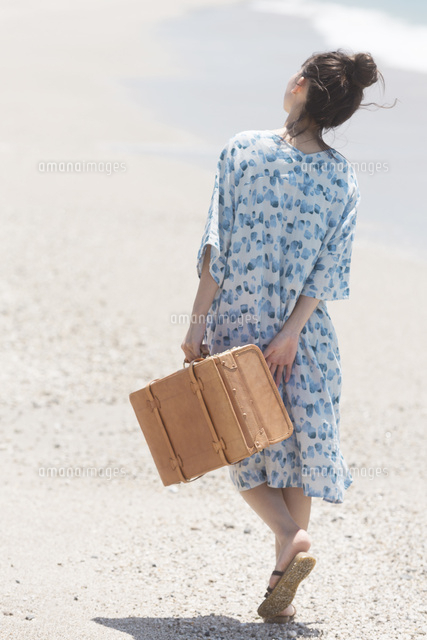 旅行鞄を持って砂浜を歩く女性 07800062274 の写真素材 イラスト素材
