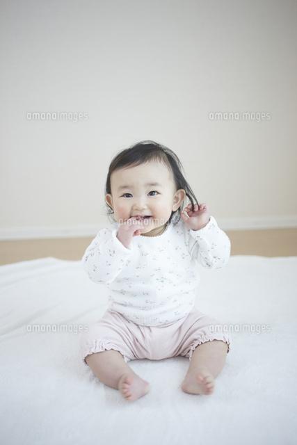 お座りをして笑う可愛い女の子の赤ちゃん10132108332の写真素材