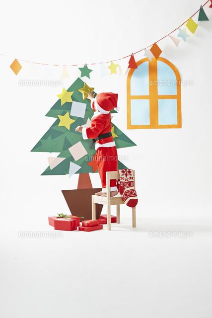 サンタクロースの格好をしてクリスマスツリーに飾りつけをする男の子