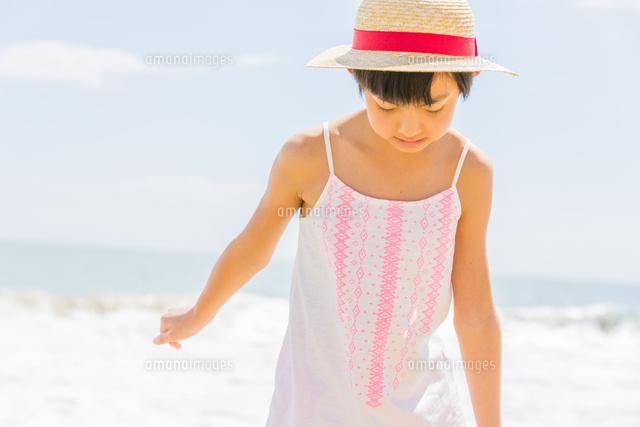 海辺で遊ぶ麦わら帽子の女の子10158005536の写真素材イラスト素材