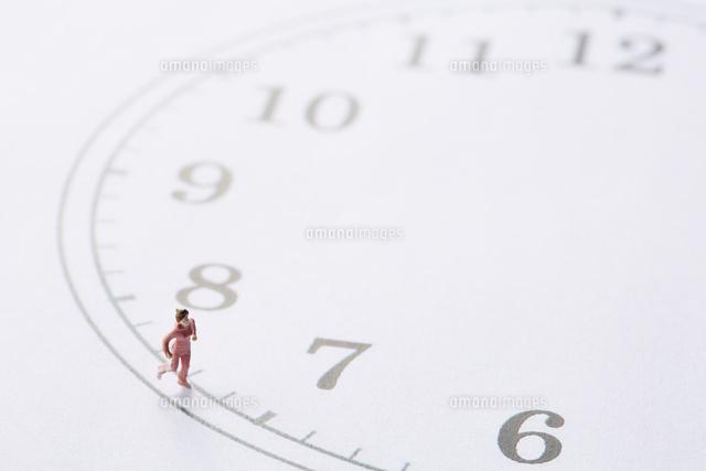 時計の文字盤の周りを走るミニチュア人形の女性10179014705の