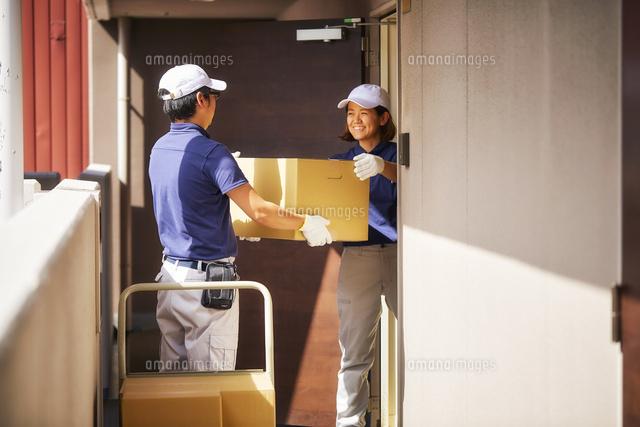 部屋から段ボールを運び出す作業服の男女[10179015052]の写真素材 ...