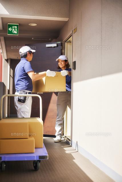 部屋から段ボールを運び出す作業服の男女[10179015053]の写真素材 ...