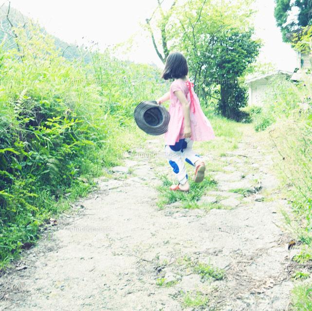 帽子を持って坂道を走る女の子の後姿10272001461の写真素材イラスト
