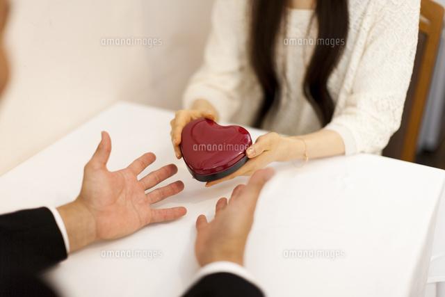 レストランでハートのプレゼントを渡す女性と男性のバレンタインデー